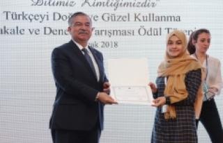 Ödülünü, Milli Eğitim Bakanı İsmet Yılmaz'ın...
